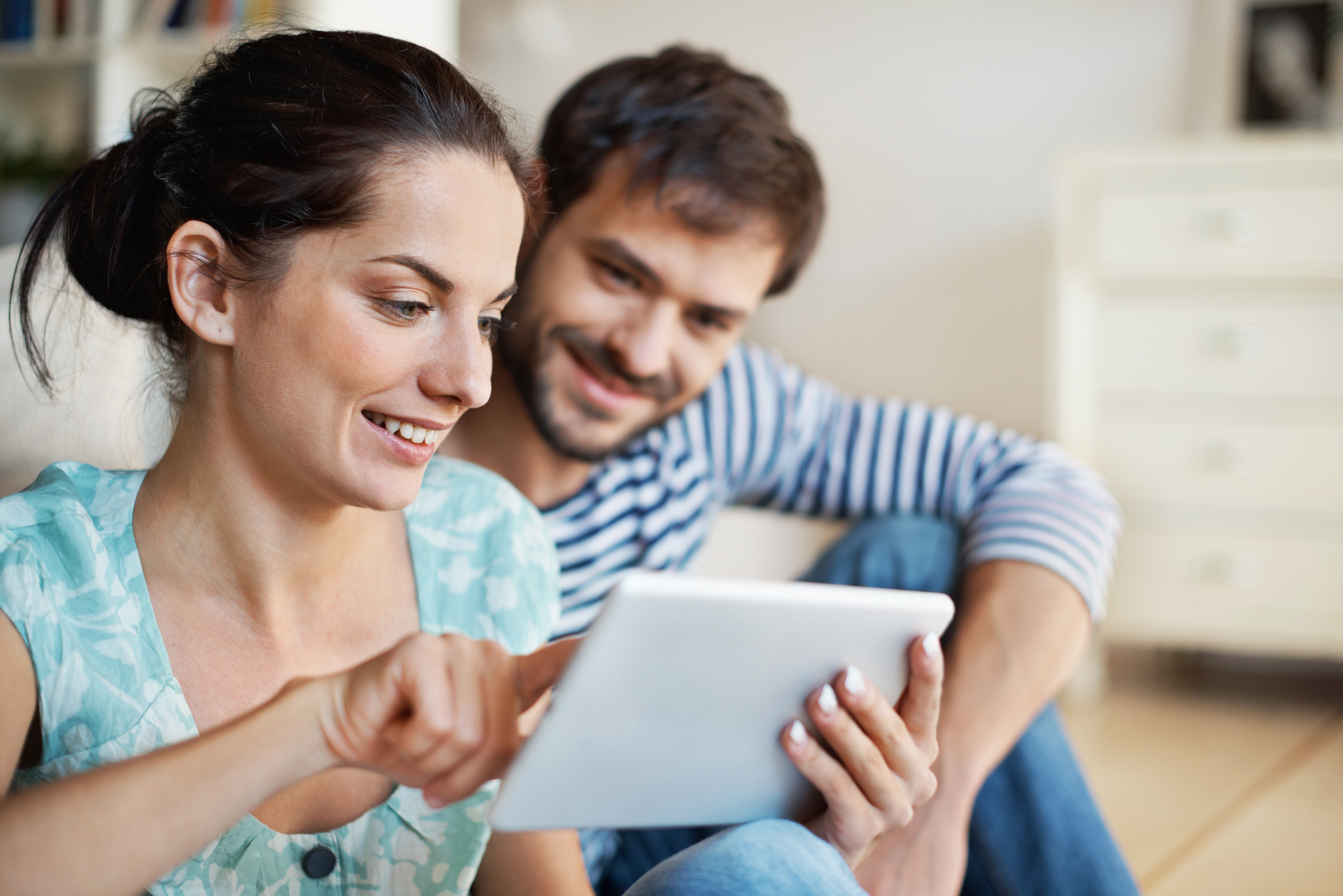 Shot of a beautiful young couple sitting together with a digital tablet at home